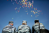 Riot police watch as a rainbow of balloons are released into the sky as several hundred LGBT activists hold a rally in central St. Petersburg to mark the International Day Against Homophobia. The rally's organisers had police permission and a promise to tighten security. In the event only a small number of homophobes turned up to protest at the rally. /Felix Features (MANDATORY CREDIT   photo: Mads Nissen/Panos Pictures /Felix Features)