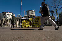 A noontime pedestrian passes by Pro-Life advocates displaing signs on the sidewalk at a rally at the Statehouse in Columbus, Ohio, Monday, Nov. 23, 2006 on the 33rd anniversary of the Supreme Court Roe v. Wade decision.<br />