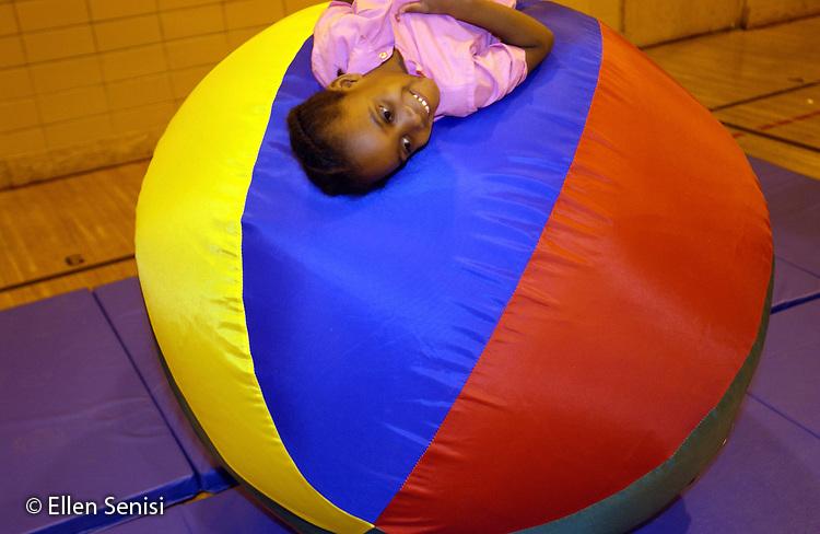 MR / Schenectady, NY                                  .Yates Arts-in-Education Magnet School (urban school).Pre-Kindergarten class; NYS Universal Pre-K Program.Girl (5, African-American) lying on big ball (held from back by gym teacher)..Smi14.©Ellen B. Senisi