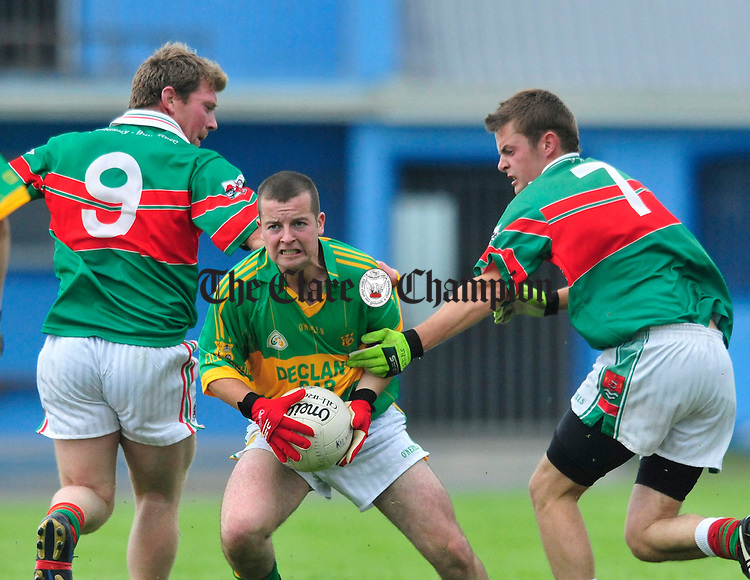 Kilmihil's Shane Egan keeps posession under pressure from Kilmurry Ibrickane's Martin O' Connor and Mark Moloney. Photograph by Declan Monaghan