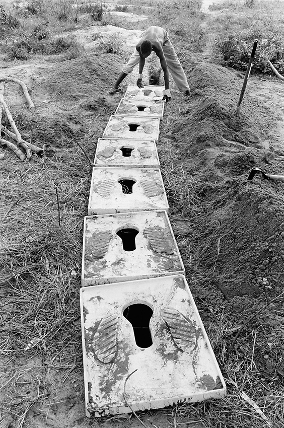 Mozambique. Province of Gaza. Chaquelane. Camp for displaced people from the town of Chokwe which was heavily flooded by The Limpopo river. A workers builds latrines for the ngo (non governmental organisation) MSF Switzerland ( Médecins Sans Frontières. Doctors without Borders) in order to avoid the spread of epidemics.© 2000 Didier Ruef