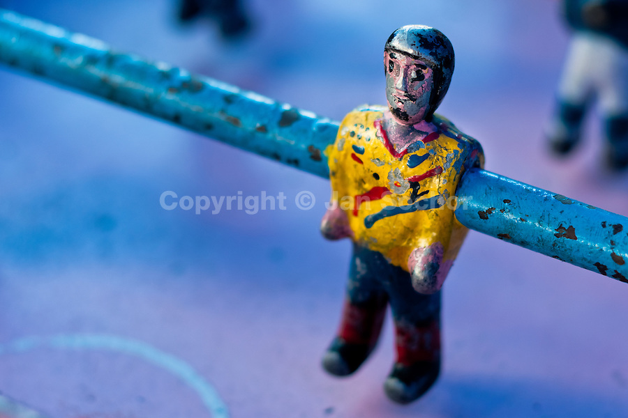 A table football player figure, with a painted yellow shirt and peeled surface, is seen inside the table football box on the street of Otavalo, Ecuador, 28 June 2010. Table football, also known as futbolin in Latin America, is a widely popular table-top game in Ecuador. During the annual fairs, the rusty old outdoor-designed tables, fully ocuppied by excited children, may be found on all public places, particularly on the squares and in the parks. Human players use figures mounted on rotating bars to kick the small plastic ball into the opposing goal. Each team of 1 or 2 human players controls 4 rows on its side of the table. The game ends when one team scores a predetermined number of goals. In 2002, the International Table Soccer Federation (ITSF) was established to promote the sport of table football.