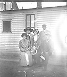 """COLLEY AND MALONE FAMILIES. Walter R. Colley (1871-1970) is pictured at right, with his son-in-law Clyde Malone (1890-1951) standing behind him. Colley's wife Lula (1875-1958) shared the bench with her husband; between them stood their daughter Izetta (1892-1966). Clyde was 20 and Izetta 18 when they married in 1910, around the time this photograph was taken. As Clyde Malone wrote in 1946, """"After graduation from high school, I was fatally bitten by the matrimonial bug and deluded Miss Izetta Colley, of the Missouri Colleys, into saying 'I do', (and she has for lo' these many years)."""" Their marriage lasted over 40 years until Clyde's death in 1951. <br /> <br /> Clyde Malone, standing at right, was born in Lincoln to Frank and Pency Malone. His father was a plasterer. Beside him is his wife, Izetta, whose parents, Lulu and Walter Colley, moved their family from Lexington, Missouri, to Lincoln in 1905. Father and son-in-law held service jobs typical of those available to black men in Lincoln in the first two decades of the 20th century--porter, janitor, waiter--before partnering to operate a grocery store in 1920-1921. <br /> <br /> Clyde then attended the University of Nebraska and graduated in 1925. Clyde and Izetta left Lincoln for about a decade while he worked as a district manager for an insurance company and then at a community center in Minneapolis, before returning to work at Lincoln's Urban League. He became executive director in 1943 and served until his sudden death in 1951. The Urban League was renamed Clyde Malone Community Center in his memory. Izetta was director of music at Quinn Chapel and played organ and sang at Lincoln's other black churches<br /> <br /> Photographs taken on black and white glass negatives by African American photographer(s) John Johnson and Earl McWilliams from 1910 to 1925 in Lincoln, Nebraska. Douglas Keister has 280 5x7 glass negatives taken by these photographers. Larger scans available on request."""