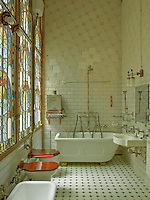 The vast stained glass window in this original bathroom overlooks the inner courtyard and bathes the room in natural light