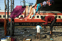 Vishal, a homeless man whose family lives by the railway tracks in Okhla, washes his young child as a train travels past, New Delhi, India