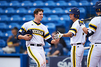 Michigan Wolverines first baseman Carmen Benedetti (43) congratulated by Cody Bruder (3) after scoring a run during the first game of a doubleheader against the Canisius College Golden Griffins on June 20, 2016 at Tradition Field in St. Lucie, Florida.  Michigan defeated Canisius 6-2.  (Mike Janes/Four Seam Images)