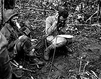 Lt. Col. John Weber, commanding officer of a Marine battalion on Cape Gloucester, sitting on his helmet, receives a report from one of his company commanders.  Pfc. Vincent Miley, looking on, blows cigarette smoke out of his nose.  January 1944. Brenner. (Marine Corps)<br /> Exact Date Shot Unknown<br /> NARA FILE #:  127-N-72050<br /> WAR & CONFLICT BOOK #:  1192
