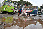 Commuter steps over a puddle at the Railways terminus in downtown Nairobi, Kenya on a rainy morning.