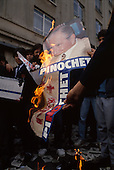 "Santiago, Chile.October 6, 1988..Burning photos of General Augusto Pinochet after he lost a vote to remain in office...In October 1988, General Augusto Pinochet ordered a plebiscite vote asking Chilean citizens whether he should continue in office. It produced a decisive ""no"" vote and the following year he lost the first presidential election in 19 years. However, under a constitution crafted by his advisors, he remained as army commander until 1998. Pinochet continued to wield enormous power until his arrest in London on human rights charges in October 1998."
