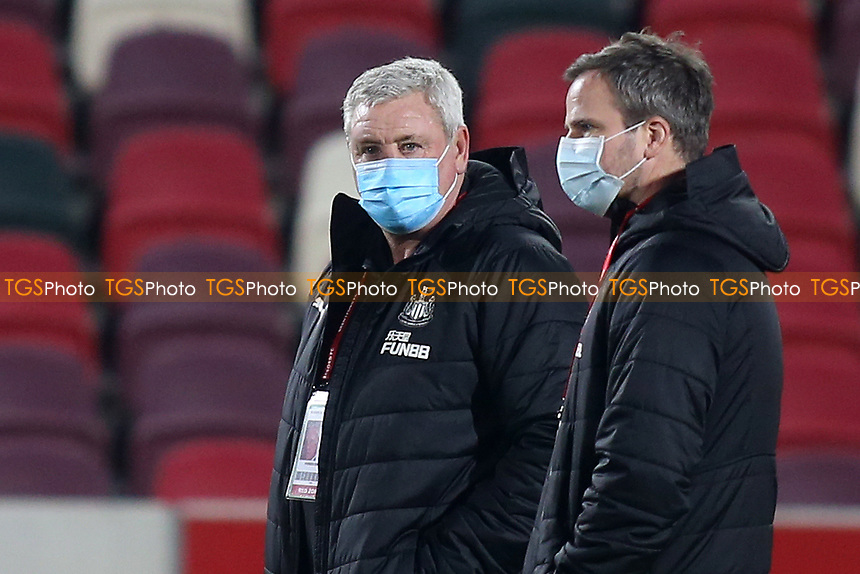 Newcastle United Manager, Steve Bruce, wears his mask as he stands alongside his first team coach, Stephen Clemence during Brentford vs Newcastle United, Carabao Cup Football at the Brentford Community Stadium on 22nd December 2020