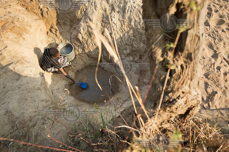 Mercy Chipeta (24) collects water from a drying pool in a river bed.