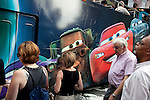 A bus with an advertisment of the movie 'Cars' goes past people waiting at lights on Broadway in the Theatre District, New York City.