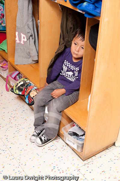 Education preschool 3 year olds separation first days of school sad boy sitting in cubby vertical