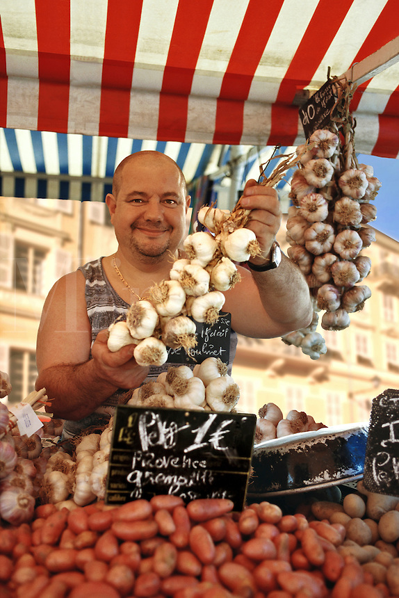 Garlic seller at market stall, Cours Saleya, Nice, France