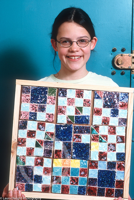 Education public school  studio art class 11 year old girl holding up ceremic tile project, smiling, proud