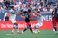 FOXBOROUGH, MA - JULY 25: Jon Bell #22 of New England Revolution comes in to tackle Emanuel Maciel #25 of CF Montreal during a game between CF Montreal and New England Revolution at Gillette Stadium on July 25, 2021 in Foxborough, Massachusetts.