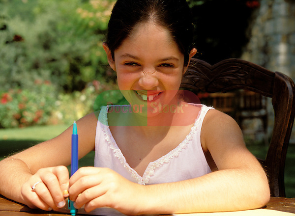 7 year old girl with large front teeth pulling a funny shy face, sitting outside at a table in the garden