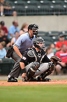 Home plate umpire Travis Eggert and San Antonio Missions catcher Austin Hedges (15) during a game against the Arkansas Travelers on May 24, 2014 at Dickey-Stephens Park in Little Rock, Arkansas.  Arkansas defeated San Antonio 4-2.  (Mike Janes/Four Seam Images)