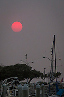 The sun glows red from smoke in the skies over the mostly deserted San Leandro Marina along San Francisco Bay.