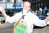 """As part of the New Hampshire Rebellion float, a man satirically dressed as """"Philmore Pawkets"""" asks for campaign donations in the Labor Day parade in Milford, New Hampshire. Republican candidates John Kasich, Carly Fiorina, and Lindsey Graham, and Democratic candidate Bernie Sanders marched in the parade."""
