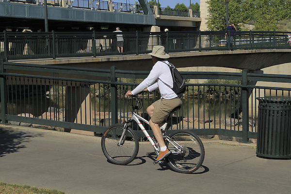 Older man riding his bike on a sidewalk in Denver, Colorado. .  John offers private photo tours in Denver, Boulder and throughout Colorado. Year-round.