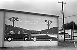Car billboard advertising a 1967 VW Beetle convertible and also a 1957 Chevy Bel Air convertible. Abernathy, Texas 1990s USA 1999