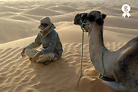 Man sitting nearby a camel on sand dune, sunset (Licence this image exclusively with Getty: http://www.gettyimages.com/detail/85071234 )