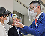 An employee wearing a face shield and face mask uses an infrared thermometer to check the temperature of shoppers at the entrance at the Matsuya Ginza department store in Tokyo, Japan on May 25, 2020. (Photo by AFLO)