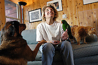 Veterinary technician Toni Schriver hangs out at home with her pets, Roxy, a German shepherd-rottweiler mix; Mousy, a domestic longhaired cat; and Phoenix, an eclectus parrot. Schriver is the founder of PAWWS to Heal (Passionate Animals Working With Survivors), a nonprofit organization that uses animal therapy to help abused and physically disabled children learn appropriate behavior and boundaries. Roxy, Mousy and Phoenix are all eager volunteers in the program<br /> <br /> Client: University of Wisconsin-Madison<br /> © UW-Madison University Communications 608-262-0067<br /> Photo by: Michael Forster Rothbart<br /> Date:  1/06   File#:  D100 digital camera frame 1302
