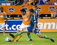 Houston Dynamo forward Brian Ching (25) strikes the ball as Seattle Sounders defender Patrick Ianni (4) attempts to block.  Houston Dynamo tied Seattle Sounders 1-1 on August 23, 2009 at Robertson Stadium in Houston, TX.