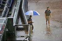 Head groundskeeper Greg Burgess of the Greenville Drive carries an umbrella as he wades through a soggy Fluor Field at the West End before a game against the Savannah Sand Gnats on Friday, September 4, 2015, in Greenville, South Carolina. The game was eventually postponed, with up to 18 inches of water in the dugouts. (Tom Priddy/Four Seam Images)