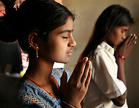 "Akshata Jivoji (left) and Malashri Kamble perform their morning prayers in their hostel room at Vimochana Sangha's school for the children of Devadasis in Malabad, India.  The school, which was founded in 1990 by Mr. B.L. Patil, is the first residential school established to break the cycle of the Devadasi system.  Because the belief is that all female children of Devadasis should themselves become Devadasis, the school was created to remove the children from the culture in which this practice took place and instead offer them an education.  All students receive free tuition, books, uniforms, food and medical care. Graduates have gone on to become teachers, nurses, engineers etc.  ""Most importantly, more than 300 girl chidren are married and living in the mainstream of society,"" says Patil proudly.  ""This doesn't seem like an achievement for others but for us, this is proof that this generation has been prevented from following their mothers into the Devadasi system,""."