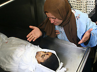 "Palestinian woman look at her sun Wissam  Kafarne, eight  years old respectively, are seen in the morgue at the local hospital in the northern Gaza Strip town of Beit Hanun after being killed when a shell they were playing with detonated, 07 August 2007. The two Palestinian children were killed after an Israeli shell they were playing with exploded, witnesses and medics said. Eight other people, including children, were also wounded in the explosion.""photo by/Fady Adwan"""