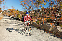 Woman mountain biking on historic gravel carriage road, Mount Desert Island, Acadia National Park, near Bar Harbor, Maine, USA
