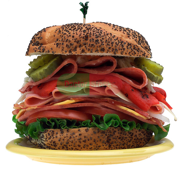 small plate with oversized large sandwich with cold cuts, cheese, pickles, lettuce, tomato on shadowless white background
