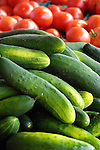 Fresh cucumbers in pile with tomatoes in background..