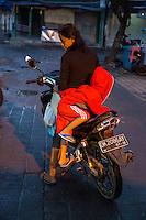 Bali, Indonesia.  Little Boy Climbing on his Mother's Motorbike.  Jimbaran Fish Market, Early Morning.