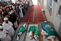 """Palestinian mourners pray near the bodies of four Palestinian children and their mother during their funeral in Beit Lahia in the northern Gaza Strip on April 28, 2008. Four children, aged one to five, their mother and a militant were killed in Israeli operations in Gaza today as Palestinian factions headed to Egypt for talks on a possible truce. The four siblings -- aged one, three, four and five -- were killed when a tank shell hit their home in the town of Beit Hanun, and their mother died later of her wounds, doctors at the Kamal Radwan hospital said.""""photo by Fady Adwan"""""""