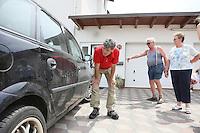 Bernd Petri (NABU Kreisvorsitzender) betrachtet die Schäden am Auto der Familie Runge
