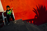 A Mexican boy plays a toy guitar while an agave succulent shadow is seen on the wall of a house in Atlixco, Mexico, 30 March 2018.