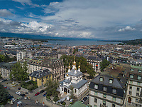 """Switzerland. Geneva. Aerial photography. The picture on Geneva town and its lake is shot from an elevated/direct-down position by an unmanned aerial vehicle (UAV), commonly known as a drone.The Russian Church (full name: Cathédrale de l'Exaltation de la Sainte Croix) is designed in a Byzantine Moscovite style. The church is a lovely 19th-century Russian Orthodox church topped with golden onion domes. The church, facade. roof and all onion domes underwent a complete revival restoration. The newly restored bulbs are gilded with golden leaves. The term gilding covers a number of decorative techniques for applying fine gold leaf to solid surfaces such as onion domes and crosses. A gilded object is also described as """"gilt"""". The Russian church serves today not only the Russian community but also Bulgarians, Serbs, Coptic Christians and other Orthodox worshippers who do not have their own church in Geneva. An onion dome is a dome whose shape resembles an onion. Such domes are often larger in diameter than the drum upon which they sit, and their height usually exceeds their width. These bulbous structures taper smoothly to a point. Drone Pilot Stefan Hess. 10.08.2017 © 2017 Didier Ruef"""