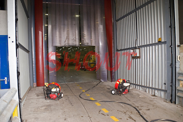 Firefighters setting up positive pressure ventilation units inside a factory unit to remove excess smoke which had been set alight by arsonists. This image may only be used to portray the subject in a positive manner..©shoutpictures.com..john@shoutpictures.com