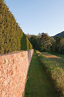 Below the gardens a neatly mown path runs along the retaining wall next to the wild flower meadows
