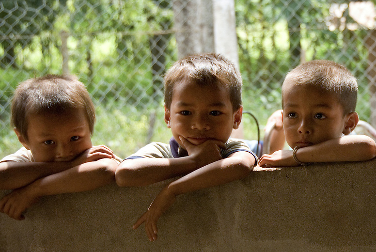Three young boys peer through a window to see what's happening. They're amazed to see westerners so interested in their small village just outside Luang Prabang, Laos.