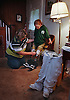 Maureen DuPre helps Brady put on her new prosthetic legs as her old pair sit in foreground. Brady must break in the new legs wearing them for an hour at a time until they stop chaffing her legs. Several visits to the doctor for adjustments must be made before they fit right. Photo by Peter Ackerman, Asbury Park Press