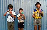 Three boys enjoy their shave ice cones, popular island treat.