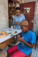 Haiti, Port-au-Prince, Artisan business, Atellier Calla , founded by Christelle Chignard Paul. Original handmade jewelry made from cow horn. Young woman working in the shop. (MR)