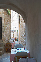 A small restaurant with outside seating on a very narrow street at the beginning of Prijeko Dubrovnik, old city. Dalmatian Coast, Croatia, Europe.