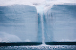 A waterfall is created by a melting iceberg, Svalbard, Norway