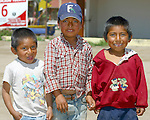 Three small Mexican children pose for a photo.